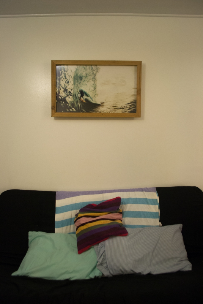 Patience pays off! After a couple of months in the new place, we upgraded from a twin bed in this space to a futon. The surfer artwork came from the dumpster at work when Reef re-did their retail wall and replaced this photo and frame.