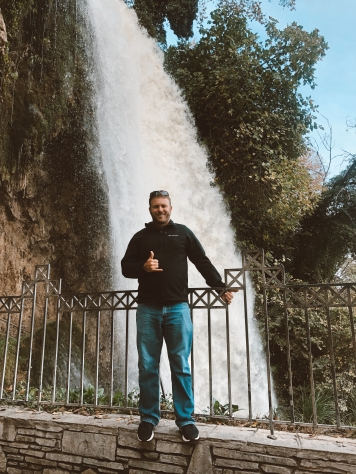A man standing in front of Edessa's waterfall