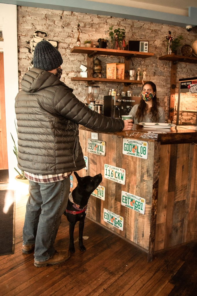 Man ordering a coffee inside Guajiros with his dog on a leash