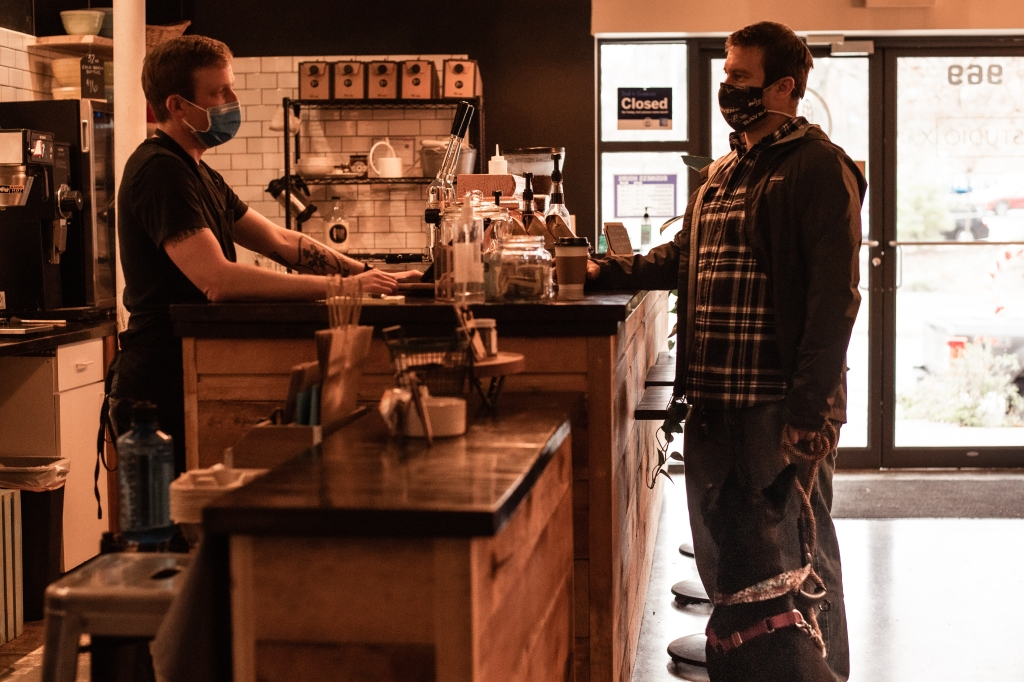 A man ordering a coffee at J-Bird coffee shop with his dog